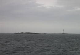 Rock way out at sea with lighthouse attatched